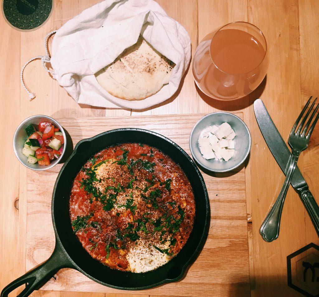 SHAKSHUKA. Huevos bochados en salsa espaciada de jitomate, acompañados de ensalada israelí, queso feta y pan pita a la leña.